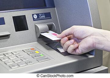 Hand taking money on ATM bank machine