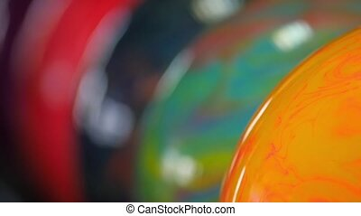 Hand taking multicolored ball from bowling ballmachine. ?amera moves the bottom up