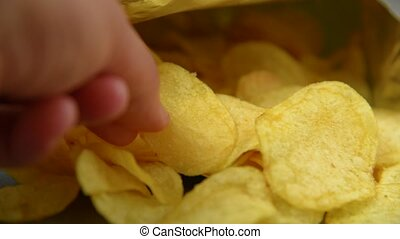 Hand taking potato chips from package. Footage for themes:...