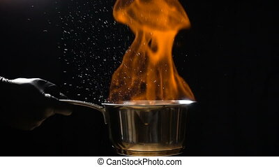 Hand that stir the pan with burning sauce and hot droplets...