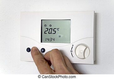 hand thermostat - hand adjusting the thermostat of a heating...