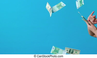 Hand throwing money cash on blue background in slow motion. ...