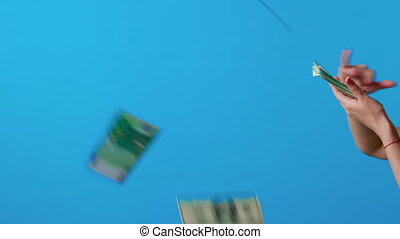 Hand throwing money cash on blue background
