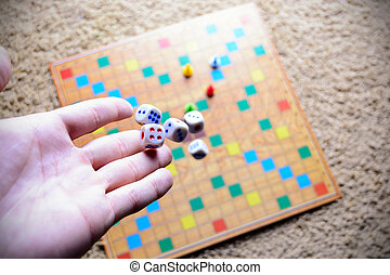 Hand throwing white dice background colorful blurred Board game. The dynamic moment of the game, selective focus.