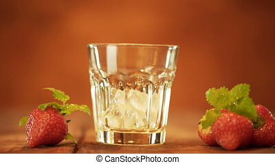 Hand throws ice cubes into a glass