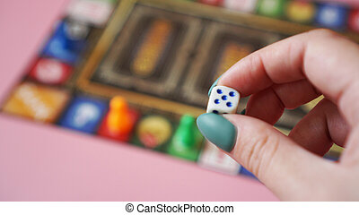 Hand throws the dice on the background of colorful blurred Board games