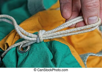 hand ties a knot of long white rope
