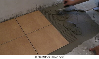 hand tile cement glue - master hand puts tile cement glue on...