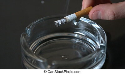 Hand tipping ash into empty ashtray in slow motion