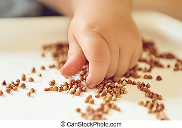 children's hand touch the croup of buckwheat