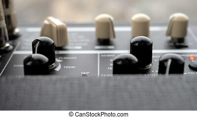 Cranking up the volume knob. Male hands twist tumblers on control panel of guitar amplifier. Amp close up