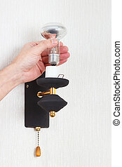 Hand unscrews incandescent lightbulb in a lamp on white wall