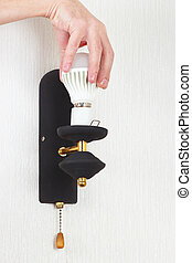 Hand unscrews led bulb in a lamp on white wall