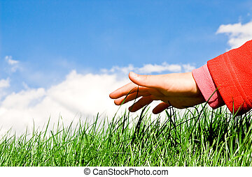 child hand reaching the grassy surface