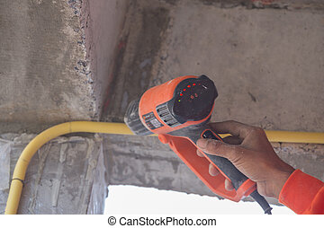 Hand use a heat gun to bending electric PVC pipe
