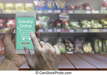 Hand use smartphone with grocery online on screen over blurred supermarket and retail store in shopping mall interior background