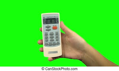 Hand using a remote control to change the temperature of air conditioner. Green screen