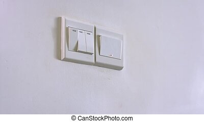 A man's right hand reaches out to press a wall switch with his thumb, turning on the lights, with sound.