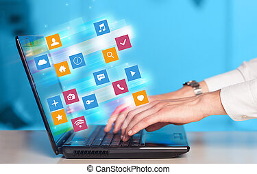 Hand using laptop with colorful application icons and symbols concept