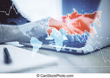 Hand using laptop with map of Russia and creative falling chart with arrow.