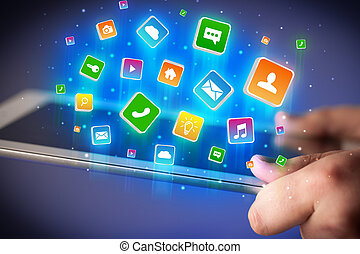 Hand using tablet with application icons flying around