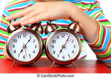 hand, von, kleiner junge, in, gestreiftes hemd, legt, auf, zwei, alarme, fokus, auf, alarme