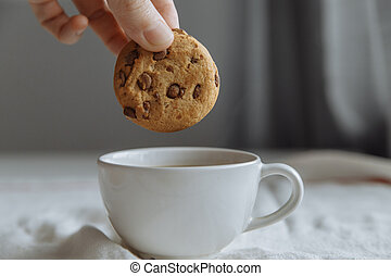 hand wants to dip brown cookies in a glass with coffee.