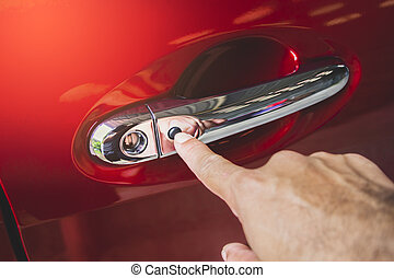 Hand was pressing to keyless entry button on the car door handle