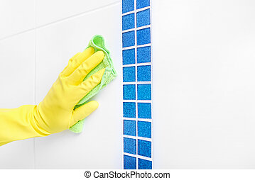 Hand wash a tile. - Hand in a yellow glove wash the tiles....