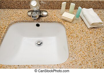Hand wash basin with shampoo, soap and towel.