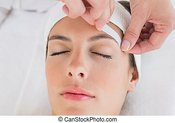 Hand waxing beautiful woman's eyebrow