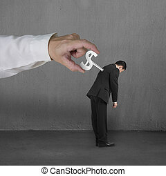 Hand windering winder on businessman's back concrete...