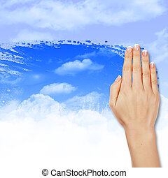 Hand wipes misted window at a blue sky