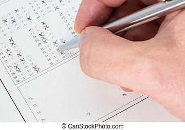 Hand with a ballpen taking an exam