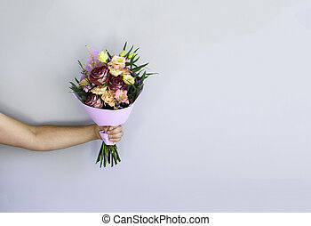 Hand with a bouquet of flowers.