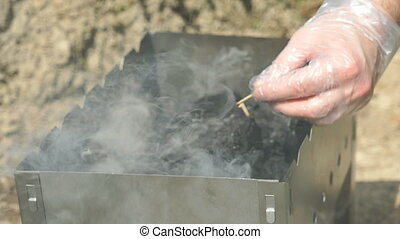 Hand with a burning match ignites the charcoal