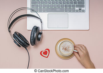 Hand with a Cup of coffee, a laptop and headphones on a coral background. Job.