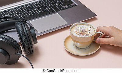 Hand with a Cup of coffee, a laptop and headphones on a pink background. Job.