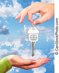 Hand with a home key. Over blue sky background.