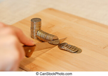 Hand with a knife cutting a pile of coin. Concept of budget cuts, savings, recession. The division into parts. Taxes. Interest rate.