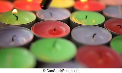 Hand with a lighter lights colorful candles. - Hand with a...