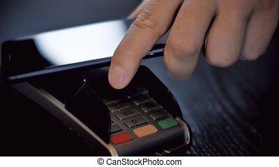Hand with a smart phone using the terminal for payment by NFC technology