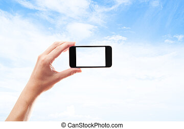 hand with a smartphone on white background blue sky with clouds