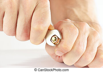 Hand with a spanner to tighten the nut