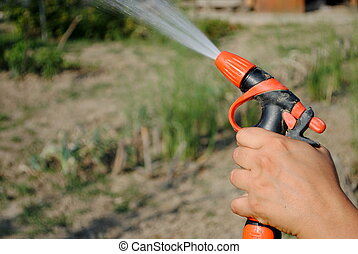 hand with a water gun in the garden