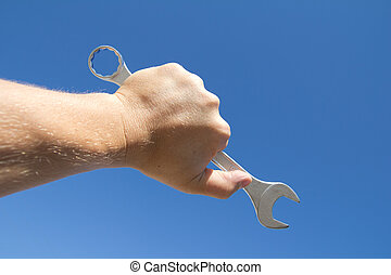 Hand with a wrench on a background of the sparkling sky.