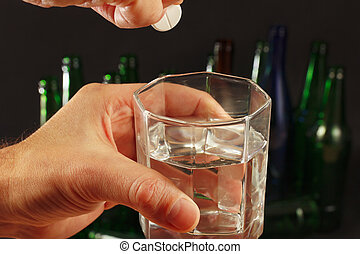 Hand with an effervescent pill from hangover over a glass of water on dark background.