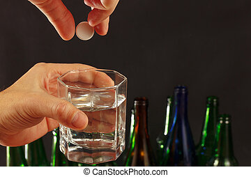 Hand with an effervescent tablet from hangover over a glass of water on dark background.