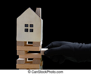 hand with black glove damaging the foundation of a house and the house is about to fall down