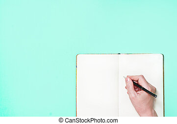 Hand with blank notepad and pen on blue background
